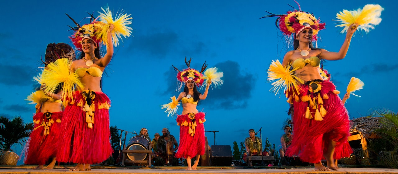 With musicians behind them, 4 Hawaiian dancers in grass skirts, elaborate headdresses and festive adornments entertain on stage.