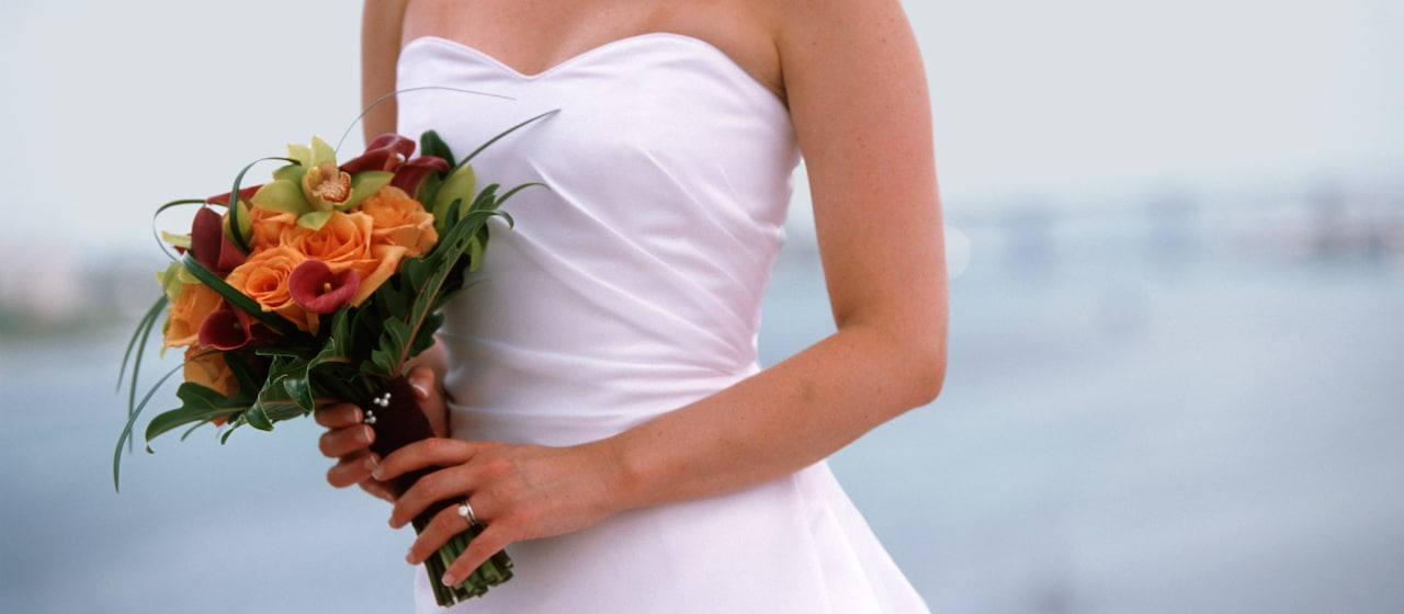 A woman in a strapless bridal style dress holds a bouquet of roses and orchids in her hands.