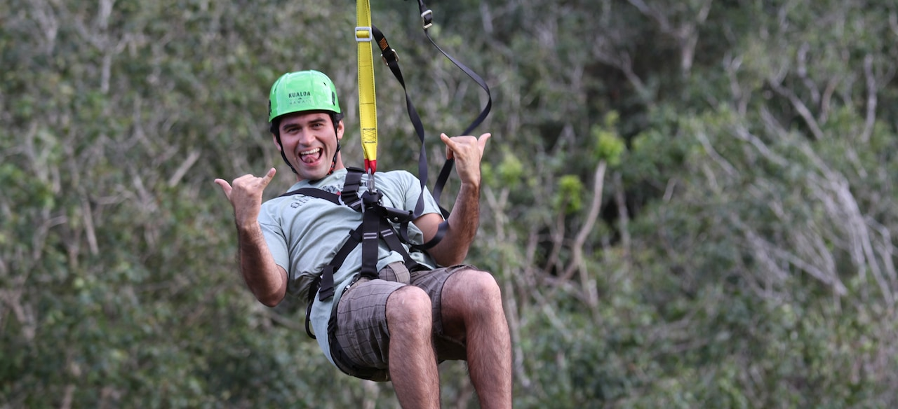 A smiling young man in a helmet and harness hangs from a zip line giving hang-loose hand signals