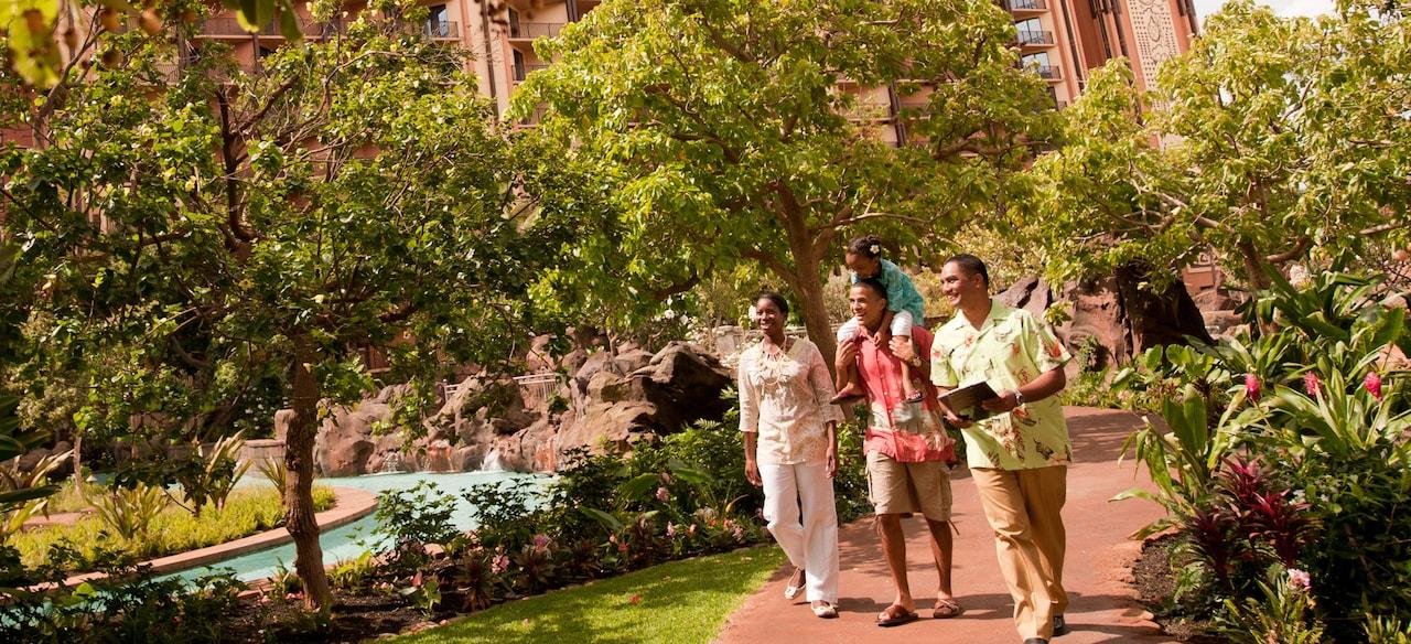 キャストメンバーのガイドに従って木や花に囲まれた道を行く母親、父親とその肩に乗った女の子