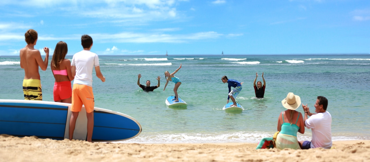 A preteen boy and girl learn to surf from 2 instructors, with their parents and friends cheering