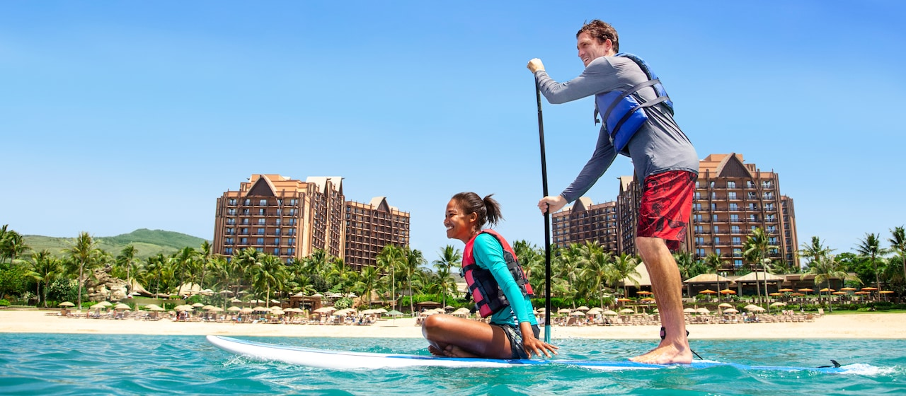 In the lagoon at Aulani Resort, a man stands and paddles a paddleboard as a woman rider sits on hers