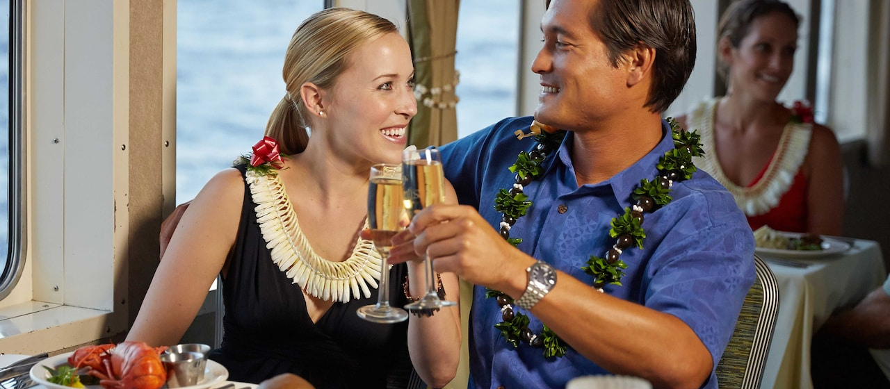 A man and woman sit in a restaurant, drinking champagne