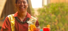 A smiling server carries a tray of cocktails