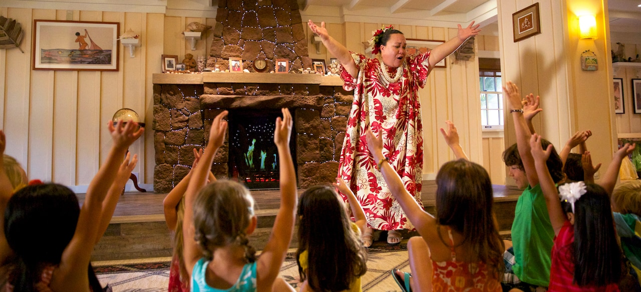 A woman in traditional Hawaiian dress leads a group of children in song and movement