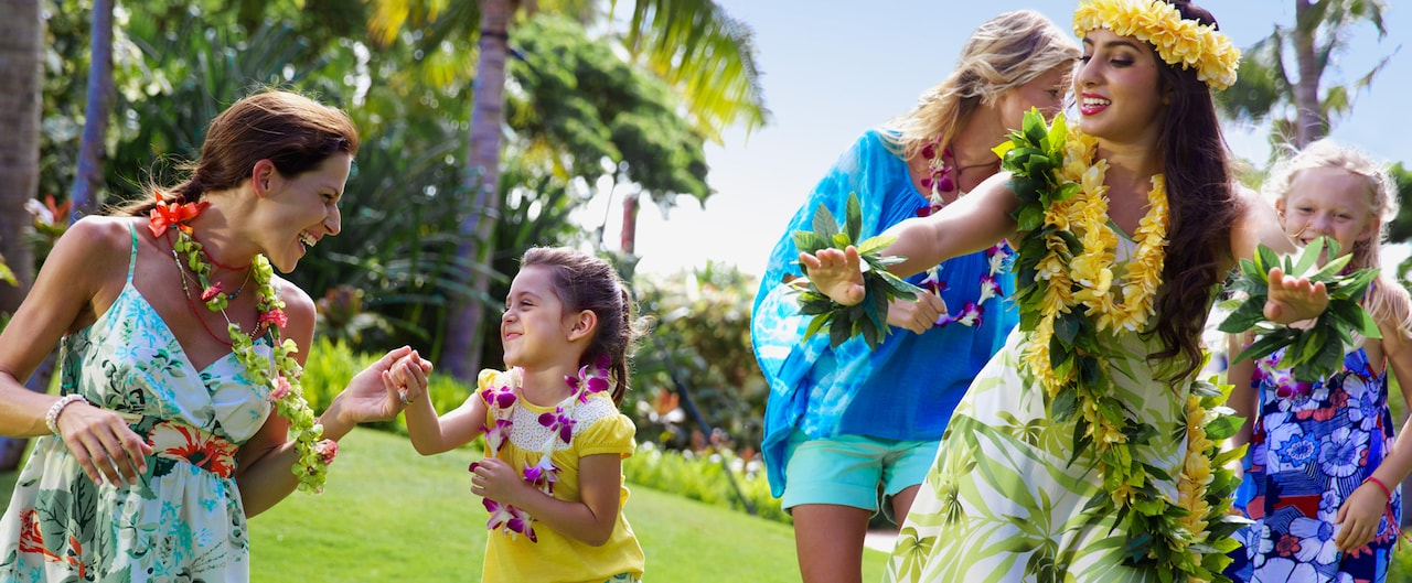 Two mothers and their young daughters learn dance moves from a female Hawaiian dancer
