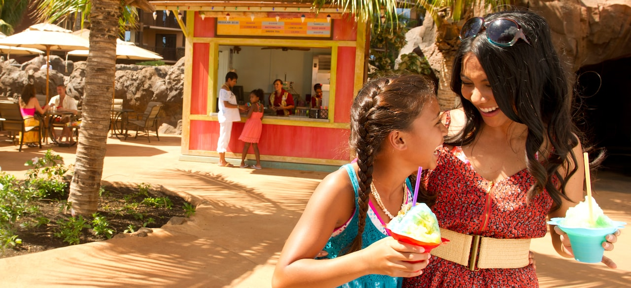 A mother and daughter enjoy shave ice desserts from a colorful nearby shack