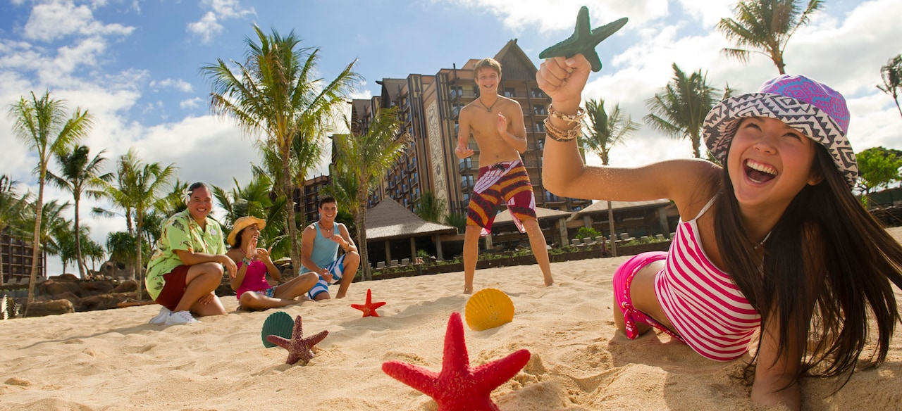 A laughing teen girl dives across sand to grab a starfish while a Cast Member and 3 young people watch