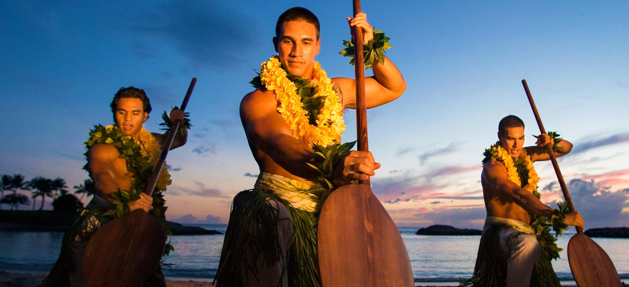 Three men wearing grass skirts, leis and maile leaves pose with large paddles on a beach at sunset