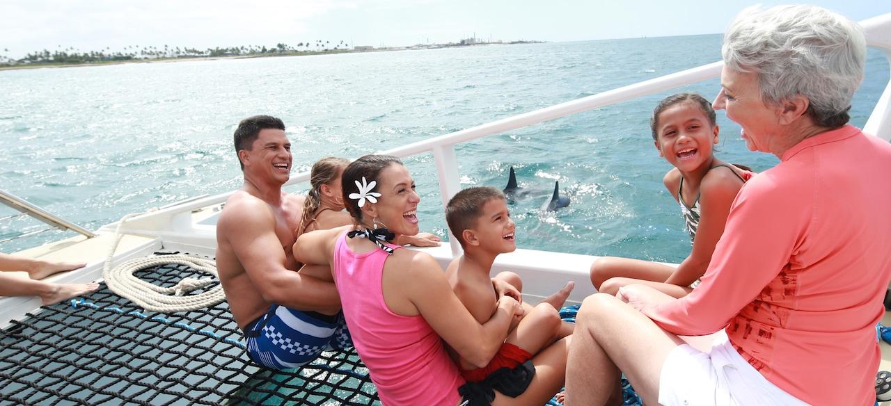 イルカがすぐ近くを泳ぐ海で双胴船エクスカーションを楽しむ祖母と両親、3 人の子供たち