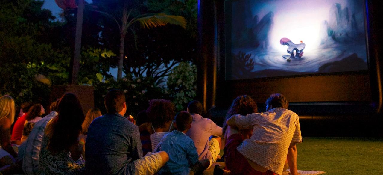 日が暮れた後、芝生に座ってスクリーンに映しだされたアニメーション映画を楽しむファミリー