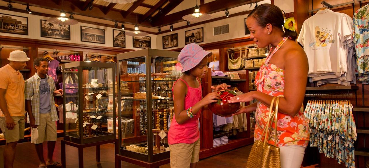 セラミックの壺を眺める母親と娘と、ジュエリーの展示ケースを眺める父親と息子