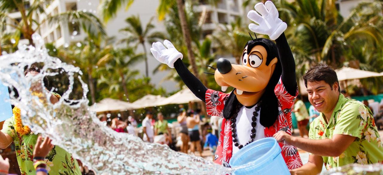 ハワイアンシャツを着て手を振るグーフィーと、バケツで水を投げかけるキャストメンバー