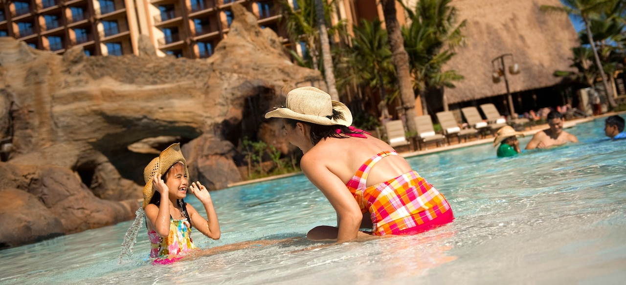 A mother and daughter, both wearing straw hats, play in the shallow end of a pool with rock caves