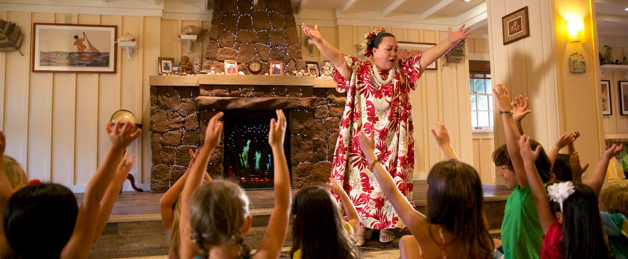 A woman in Hawaiian garb and a group of children sit on the floor watching her reach to the sky