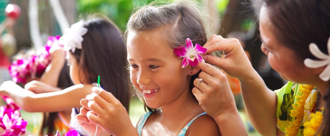 A Cast Member tucks a fuchsia orchid behind a little girl's ear as she threads flowers to make a lei
