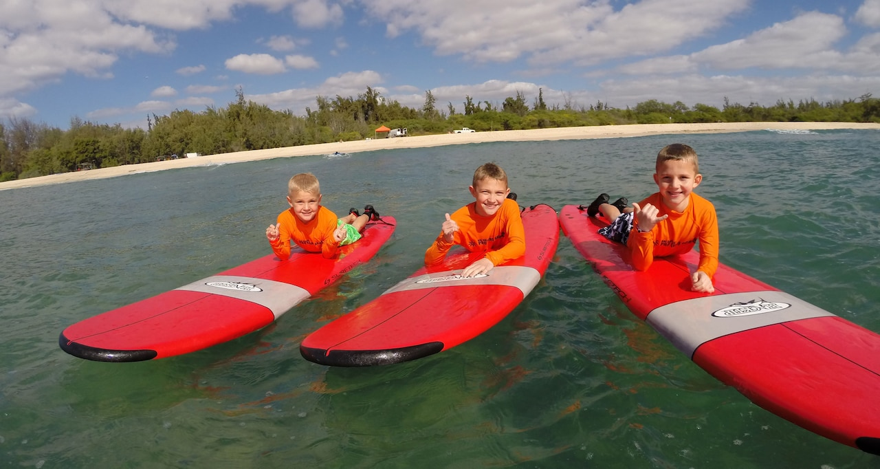 Three boys lie on their bellies on surfboards in the ocean and give the hang loose hand sign