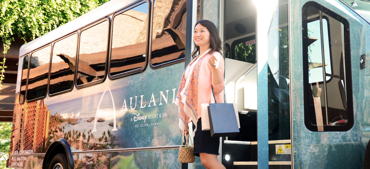 A grinning woman holding a small handbag and shopping bags in the crease of her elbow stands outside a tour bus wrapped in a photograph of Aulani, A Disney Resort & Spa in Ko Olina, Hawaii