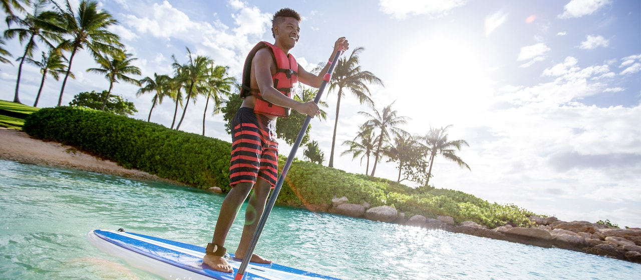 With the palm lined shore behind him a young man in a life vest and board shorts stands and paddles his paddleboard out to sea.