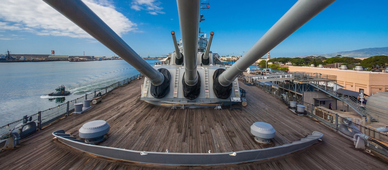 Aboard the deck of the battleship U S S Missouri, the barrels of 5 high-caliber guns are aimed skyward