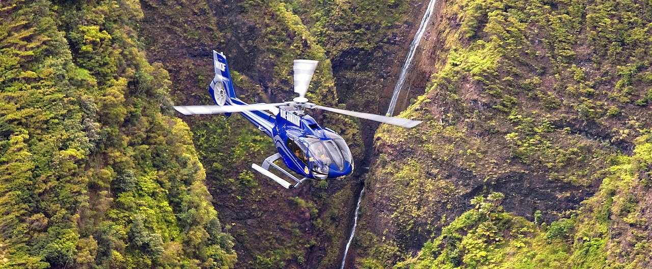 A helicopter flies by lushly forested cliffs