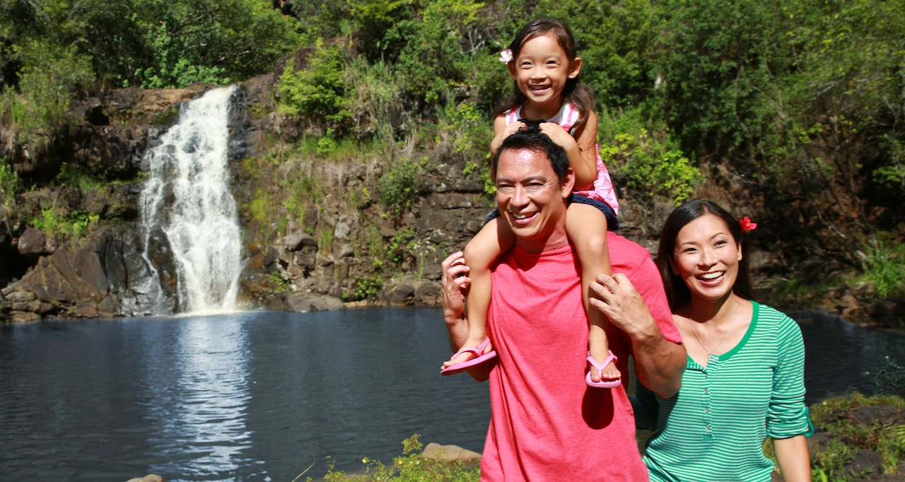 A woman and a man with a young girl on his shoulders walk beside a pond near a waterfall