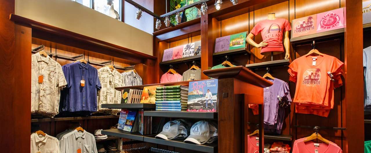 Aulani caps and books about Hawaii on a shelf, with men's shirts and tees hanging nearby