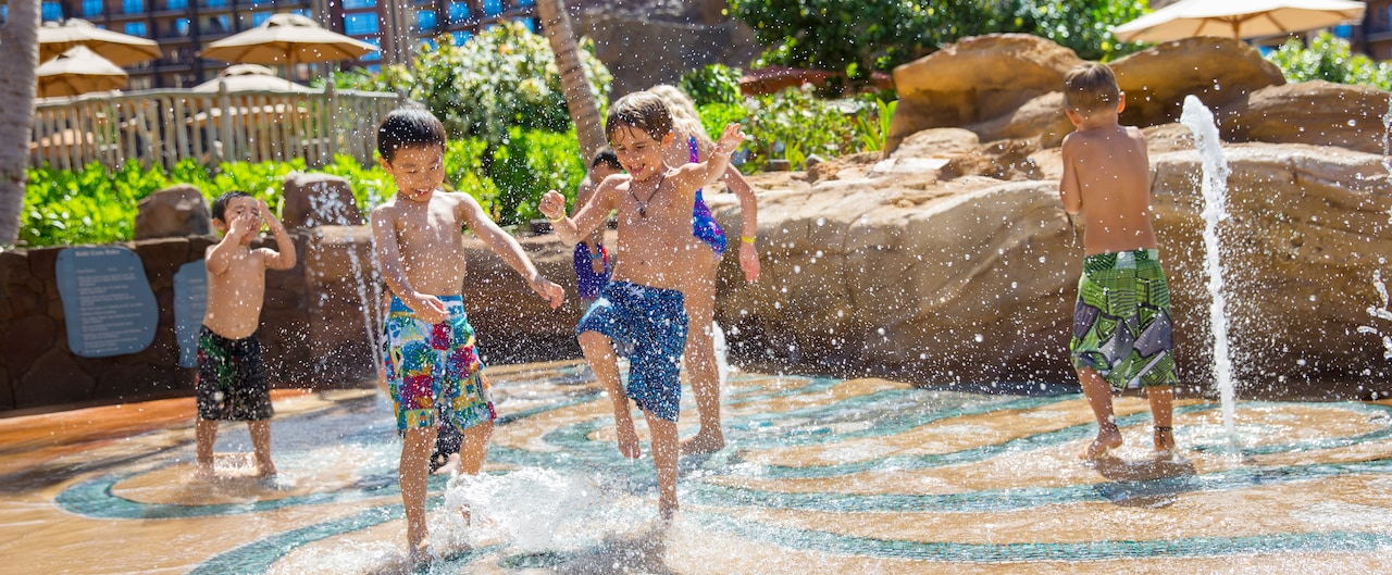 Two small boys in swim shorts play around squirting water jets near 4 more playing children
