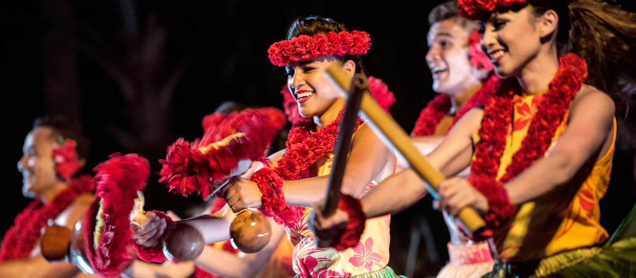 A close up of Hawaiian dancers in leafy skirts, leis and head dresses playing traditional island instruments made of bamboo, coconuts and flowers.