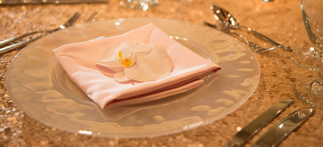 A place setting decorated with a satin napkin and orchid on a table covered in gold sequins