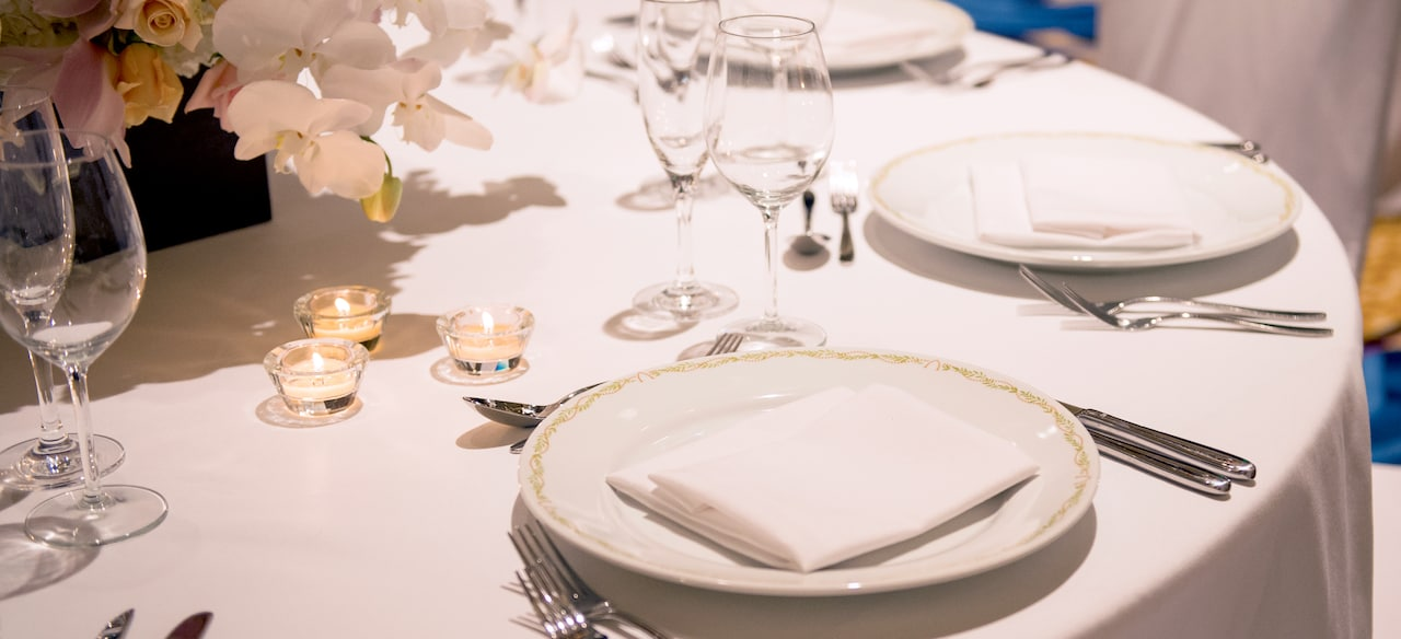 Two place settings on a table with white linens, flatware, stemware, votive candles and a floral centerpiece