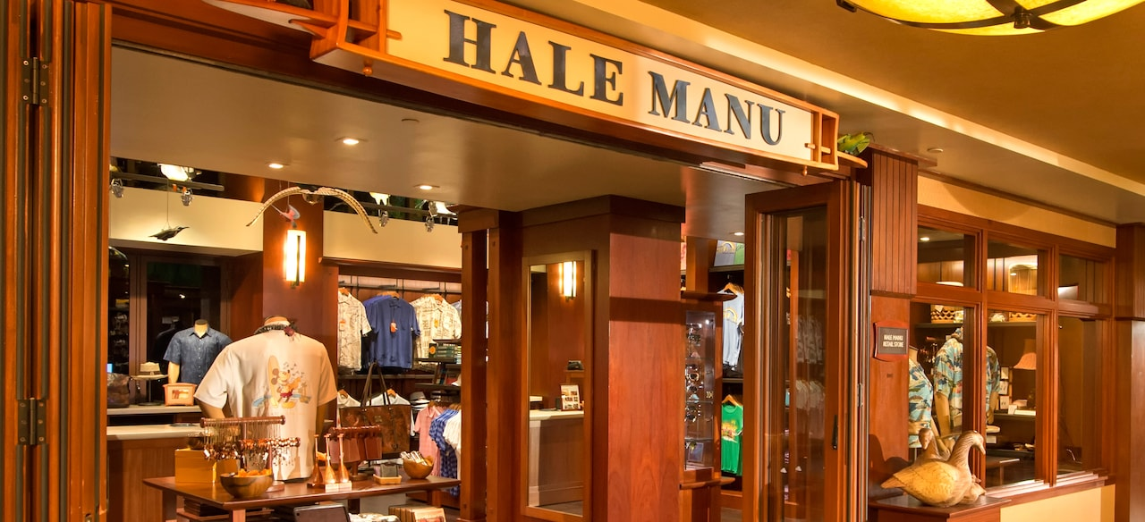 The wood-paneled exterior of Hale Manu boutique, with displays of resort wear and Hawaiian jewelry