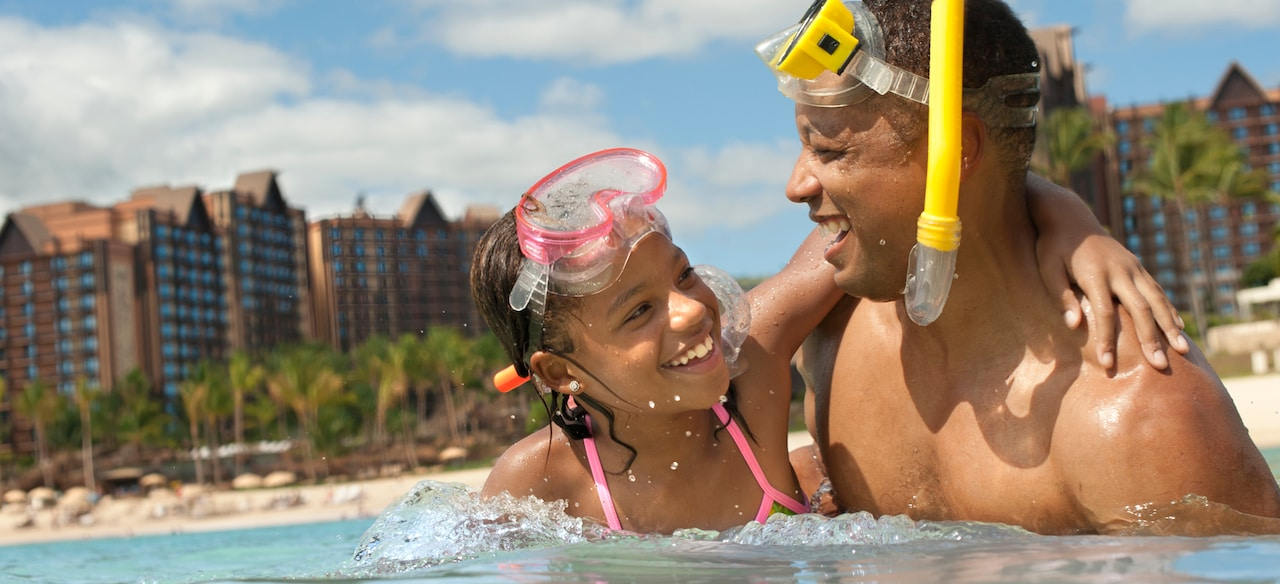 A father and daughter share a happy moment in between snorkeling in the lagoon at Aulani