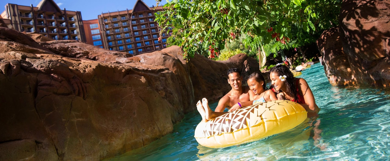 A girl on an inner tube near her father and mother along a lazy river, with rocky banks and a tree