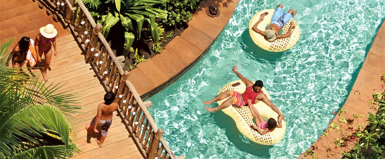A bridge and a father and daughter on an inner tube floating down a lazy river