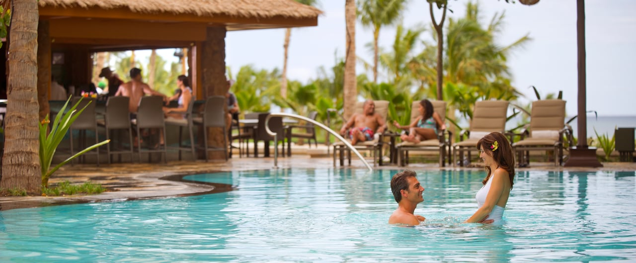 A man holds a woman by the waist in a pool while couples lounge on chairs and drink at the bar
