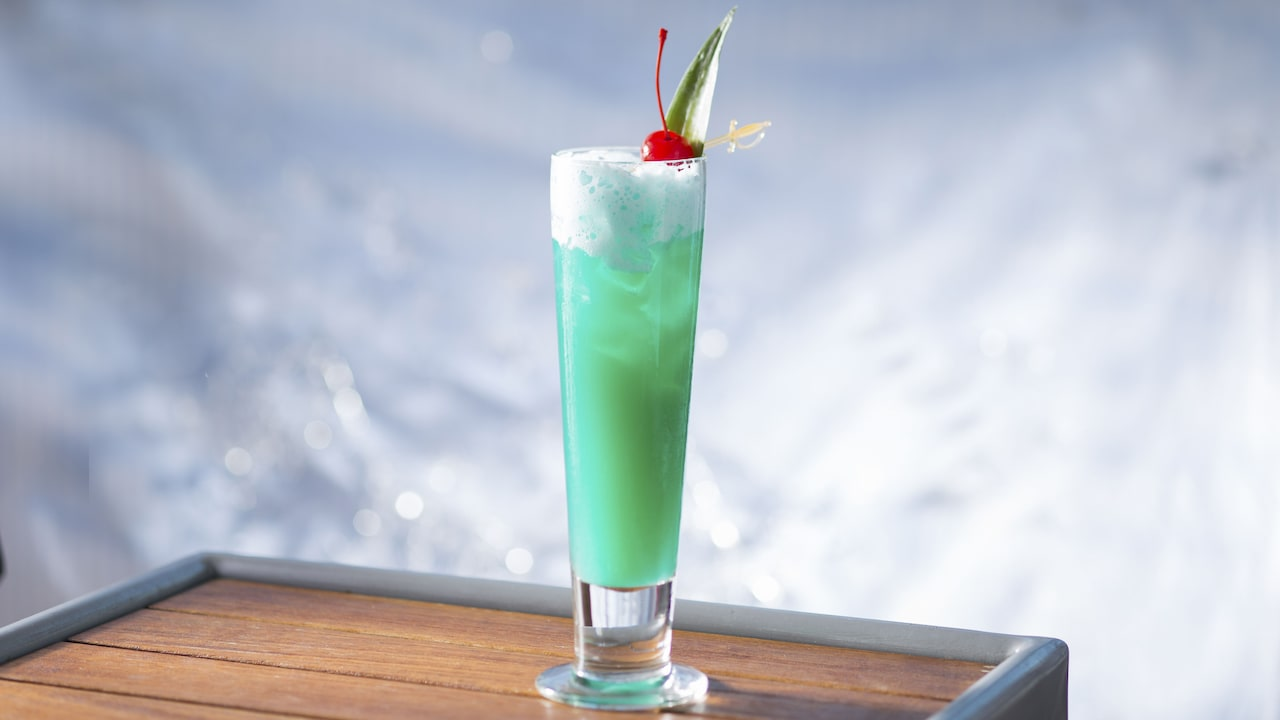A tall tapered glass containing a Blue Hawaiian cocktail on the rocks is garnished with a maraschino cherry and a pointed leaf skewered by a miniature plastic sword