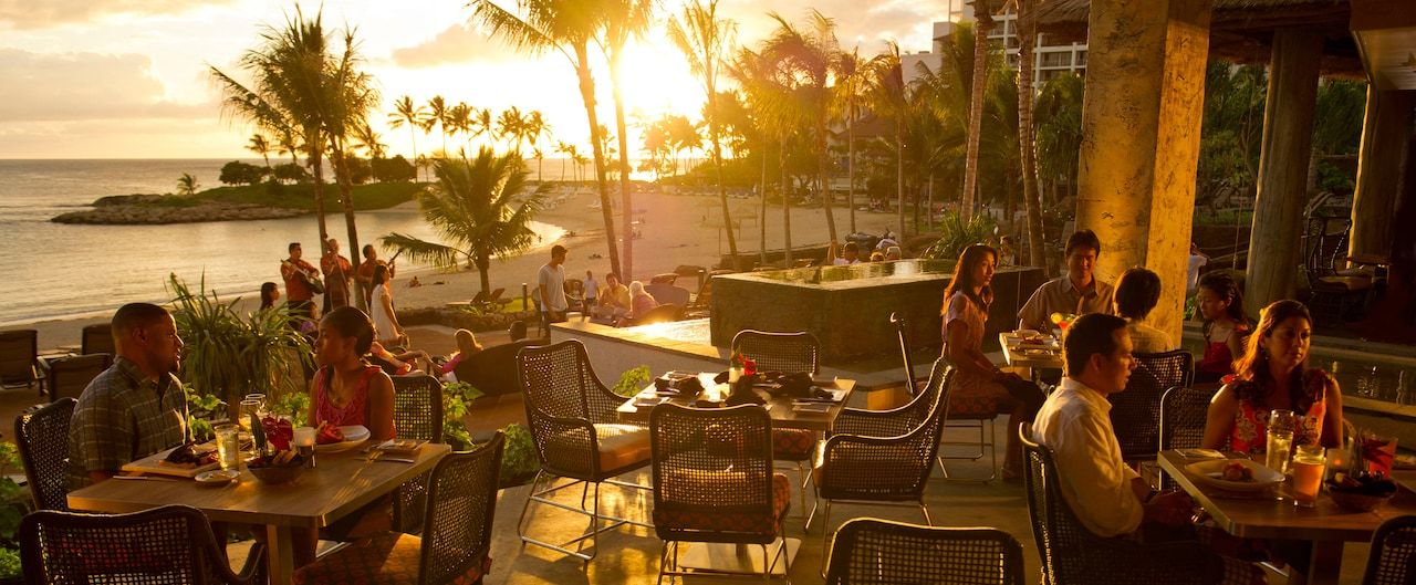 Two couples and a party of 4 dine on an outdoor patio surrounded by palm trees and ocean at sunset