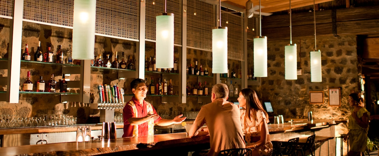 A smiling bartender talks to a couple seated at a bar