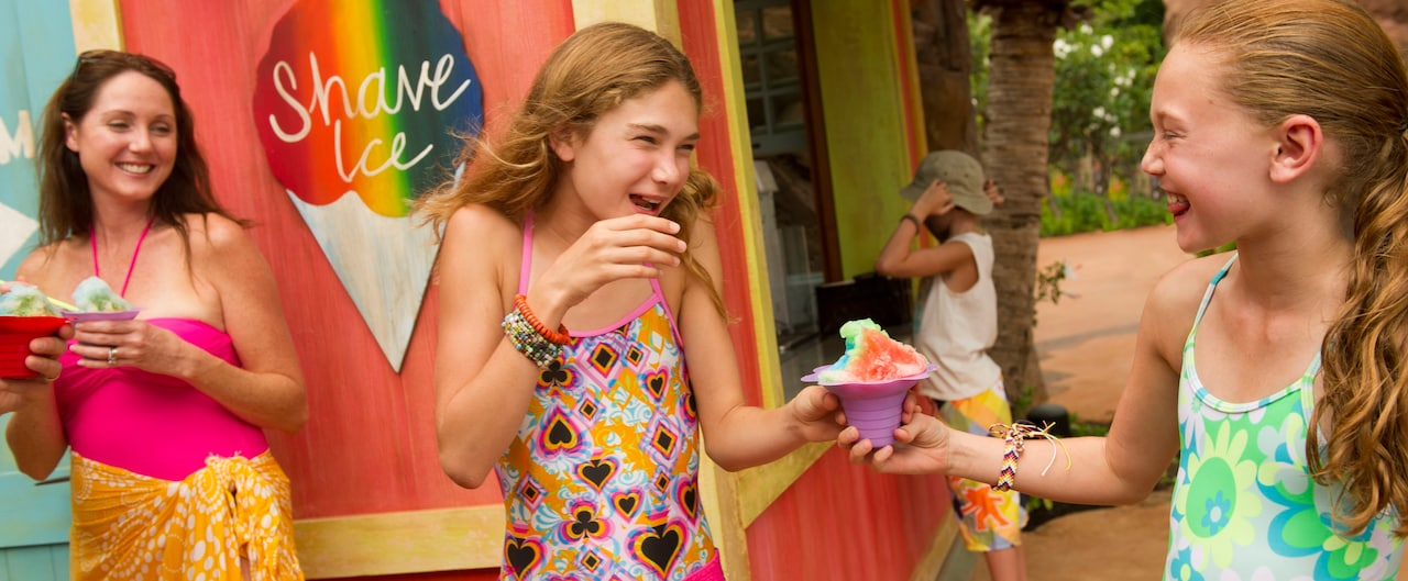 Two tween girls in swimwear clutching a shave ice dessert as a woman holding a shave ice looks on