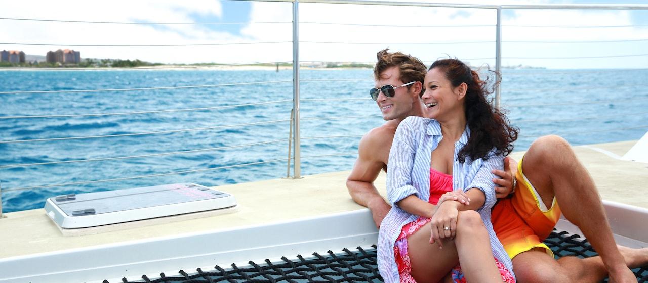 A young couple relaxes aboard a catamaran moving through a harbor