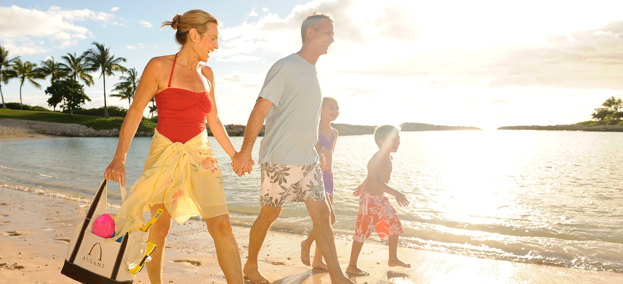 A family walks on Ko Olina Beach at Aulani
