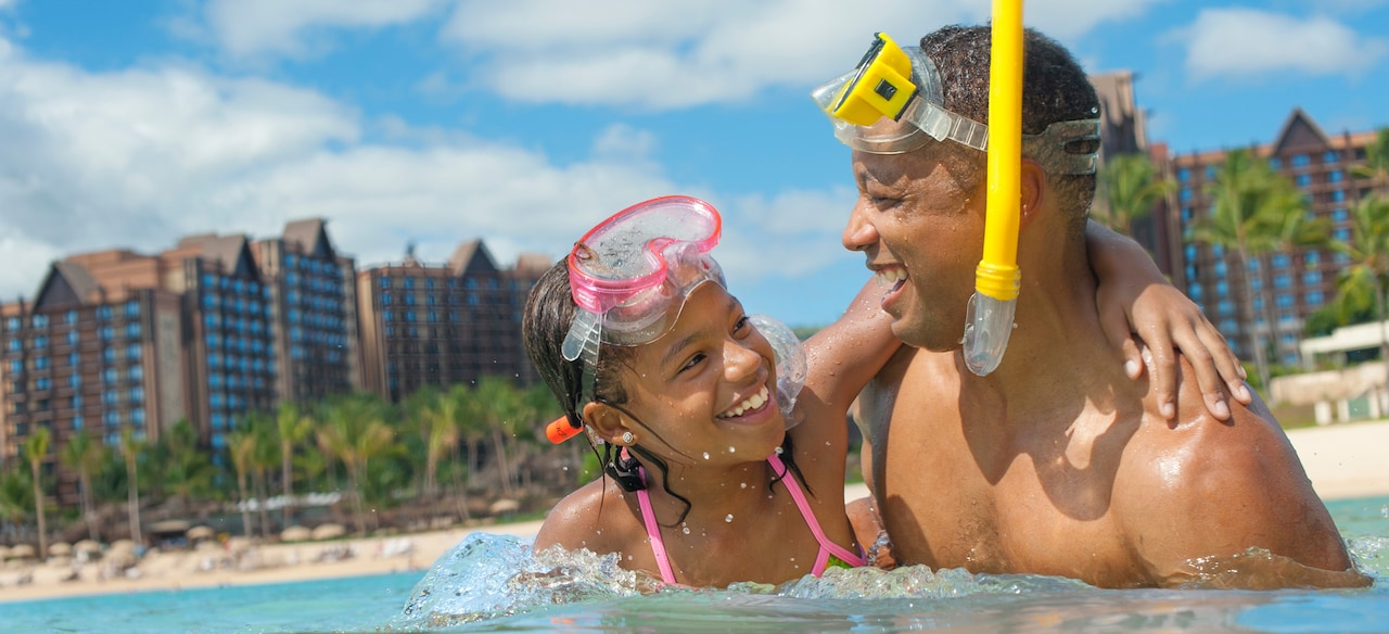 A father and daughter wearing snorkels and masks standing in the waters off Aulani
