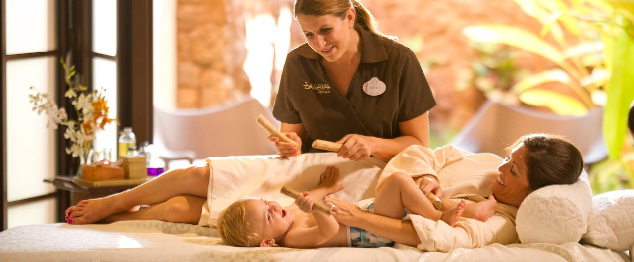 A smiling mother and baby lie on a massage table near a spa practitioner with massage sticks