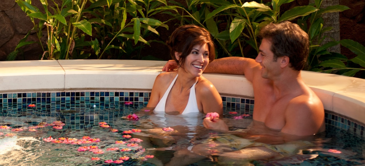 A smiling couple sits in a tiled, round pool with plumeria blossoms floating in the water