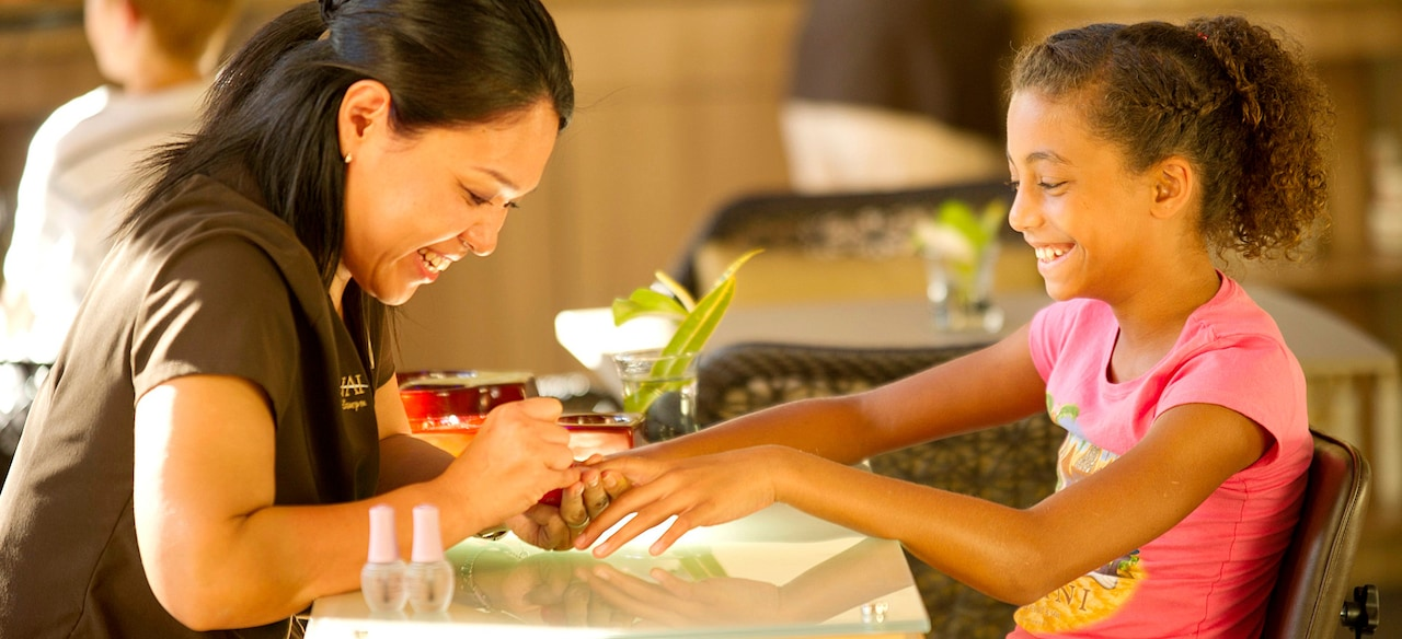 A friendly manicurist gives a grinning tween a manicure over a small glass-top table