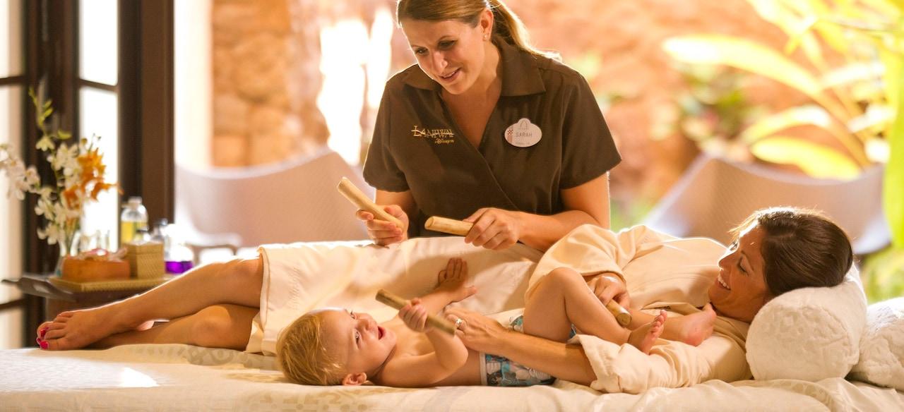 マッサージ・スティックを持った施術者と、マッサージ・テーブルの上で微笑むお母さんと赤ちゃん