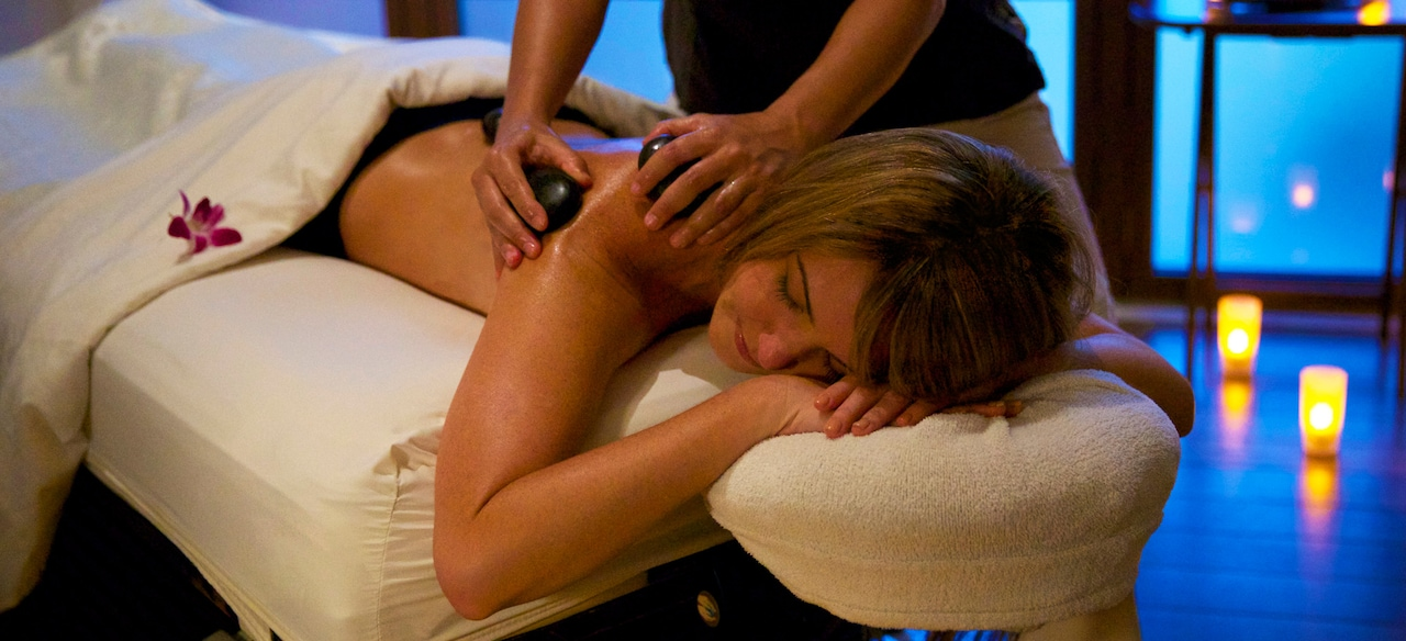 A woman lies on a massage table in a candlelit room as heated stones are applied to her back