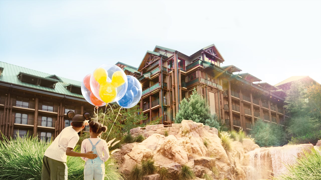 A boy and a girl with balloons standing by the fountain at Disney's Wilderness Lodge