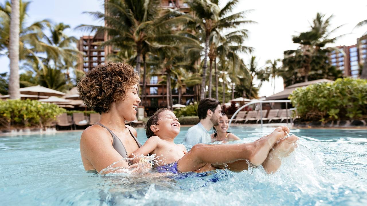 Una familia de 4 personas sonríe mientras disfruta del tiempo en la piscina Waikolohe en Aulani Resort